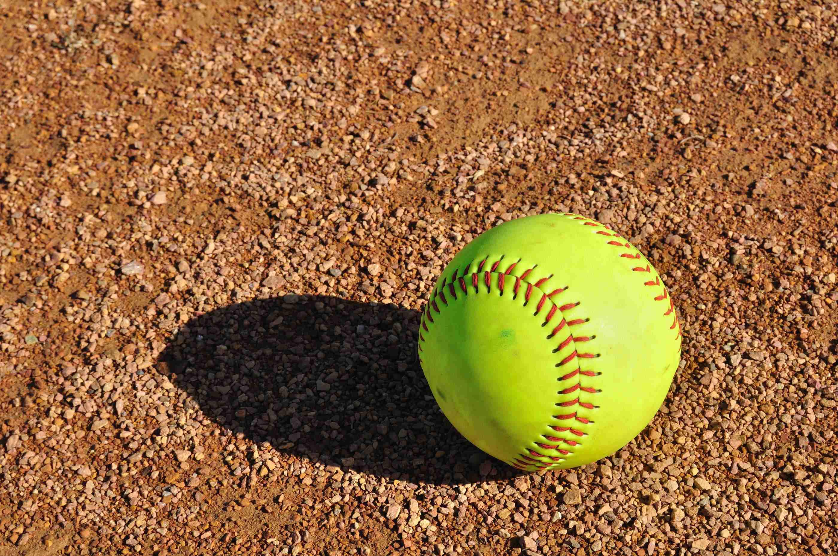 Yellow Softball Sitting on the Infield Dirt