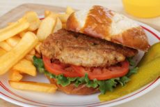Pork tenderloin lettuce and tomatoes on a bun with french fries