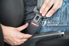 Closeup of man fastening seat belt in car