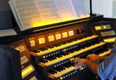 Close up view of a organist playing a pipe organ on cathedral