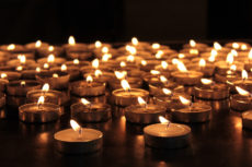 burning memorial candles on dark background .