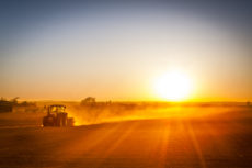 A farmer in a tractor prepares his field as the sun begins to set. The tractor is backlit by the setting sun. ** Note: Soft Focus at 100%, best at smaller sizes