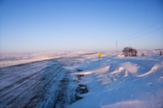 Ice covered road and snowy rural landscape.