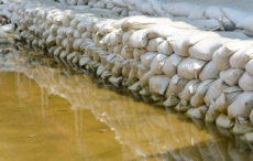 White sandbags for flood defense and it's reflection brown water.