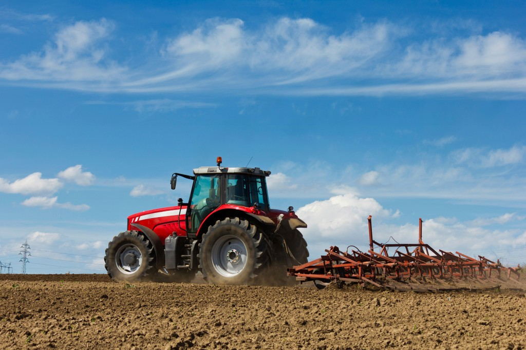 Farmer Plowing The Field. Cultivating Tractor In The Field. Red