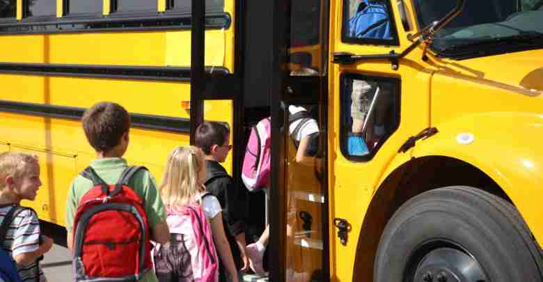 Elementary school students getting on school bus