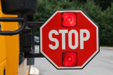 Red School bus Stop Sign out and flashing